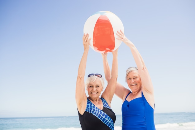 Senior woman holding beach ball