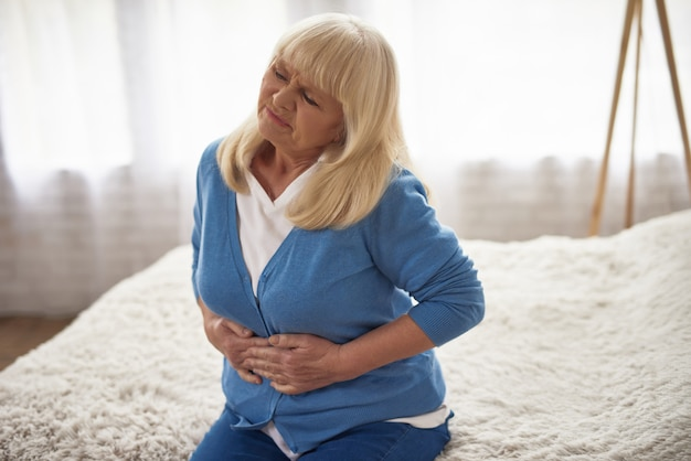Senior woman holding belly morning stomach ache.