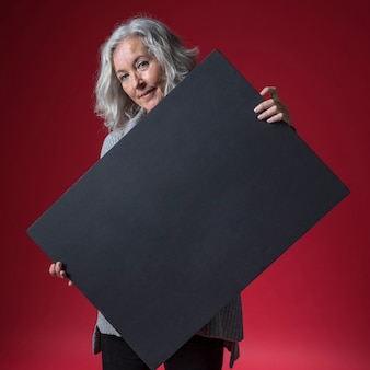 Senior woman holding blank black placard standing against red backdrop