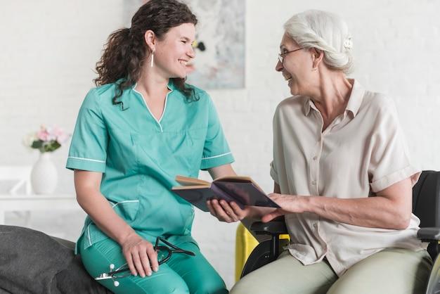 Senior woman holding book sitting on wheelchair making fun with beautiful nurse