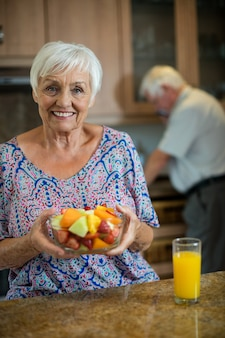 Senior woman holding bowl of fruit while man working in kitchen at home