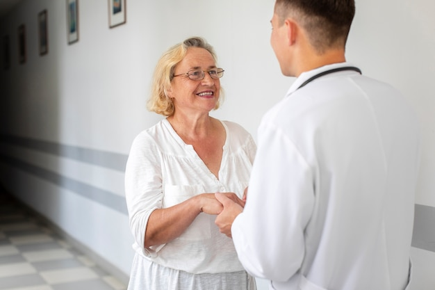 Senior woman holding doctor hands