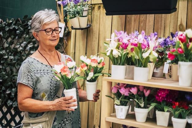 新鮮なチューリップの植木鉢を保持し、木製の棚に置く年配の女性。セラミック植木鉢を運ぶ眼鏡の老婆。新鮮な植木鉢を分析する古い女性の花屋