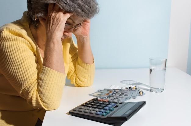 頭を抱えた年配の女性。薬とお金でテーブルに座っている年金受給者。うつ病の概念、薬価、治療費