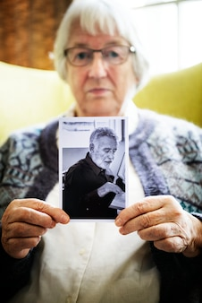 Senior woman holding a photo of a senior man