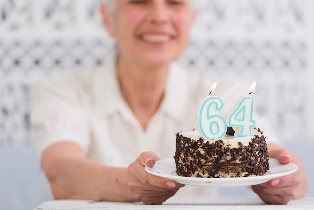 Senior woman holding plate of delicious birthday cake with glowing number candles