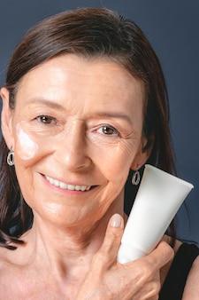 Senior woman holding a white face cream tube