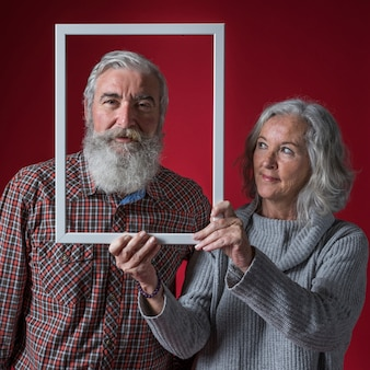 Senior woman holding white frame border in front of her husband's face against red backdrop