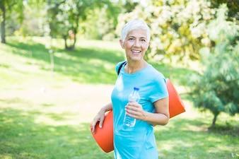 年配の女性は公園で彼女の背中にフィットネスマットを保持し、運動の準備をします。