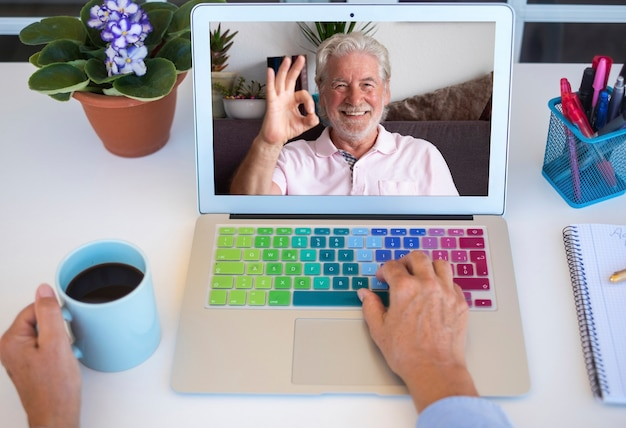 A senior woman holds up a cup of coffee during a videocall with her smiling husband - two retirees stay in touch remotely. white desktop outdoors on the terrace