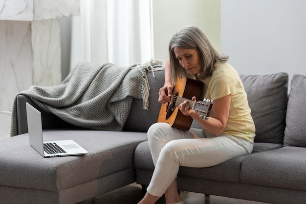 Senior woman at home on the couch using laptop for guitar lessons