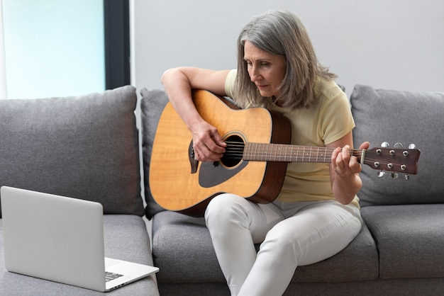 Senior woman at home on the couch using laptop for guitar lessons Free Photo