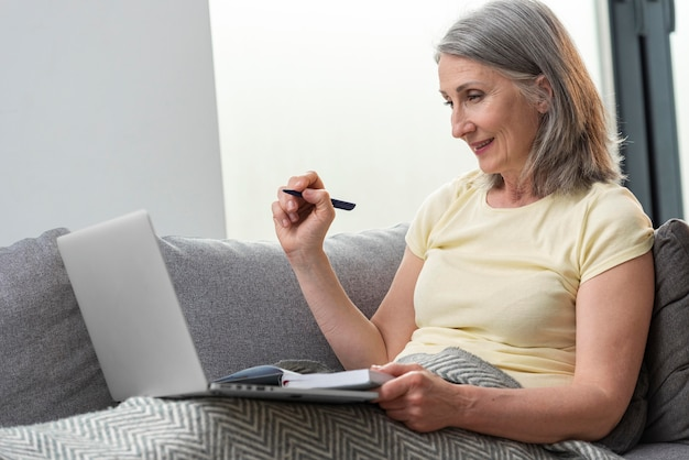 Senior woman at home on the couch using laptop and taking notes