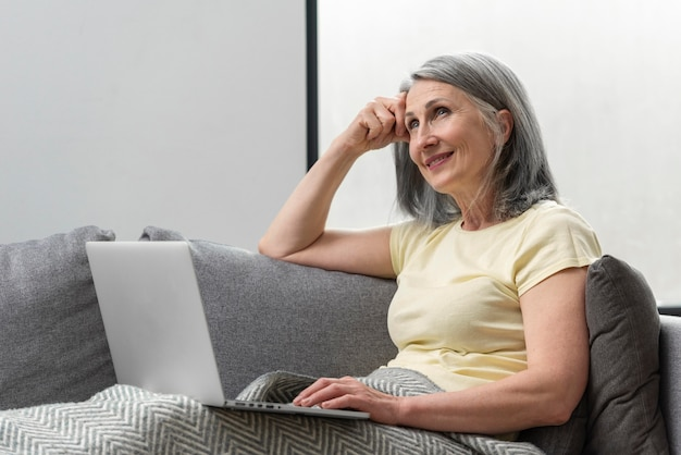 Senior woman at home on the couch using laptop