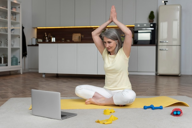 Senior woman at home taking fitness lesson on laptop