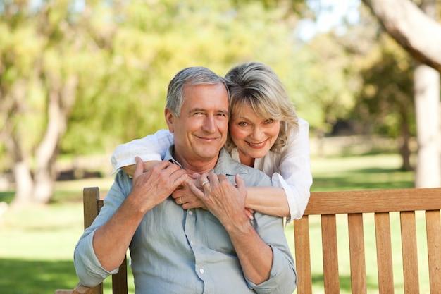 Старший женщина обнимает ее муж, который находится на скамейке