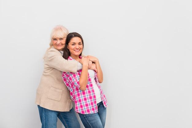 Senior woman hugging her smiling daughter against white background