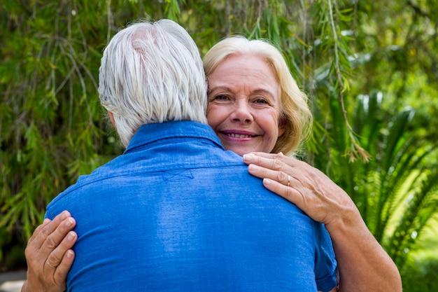 Senior woman hugging man against tree at park