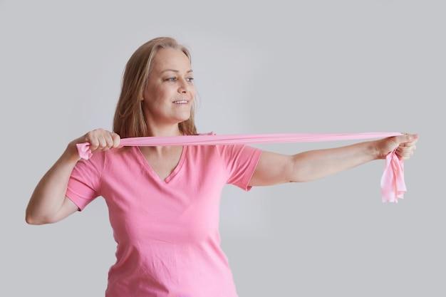 탄성 밴드와 함께 피트 니스를 하 고 분홍색 티셔츠에 고위 여자. 노년기의 건강한 생활 방식.