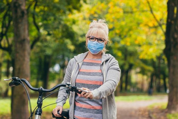 Старшая женщина в защитной маске на лице гуляет в парке с велосипедом