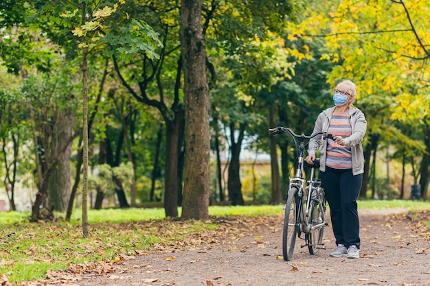 自転車で公園を歩いている彼女の顔の保護マスクの年配の女性