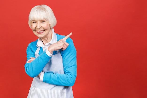 Старшая женщина в положении рисбермы изолированная на красной предпосылке. она хорошая домохозяйка. она любит готовить вкусную еду.