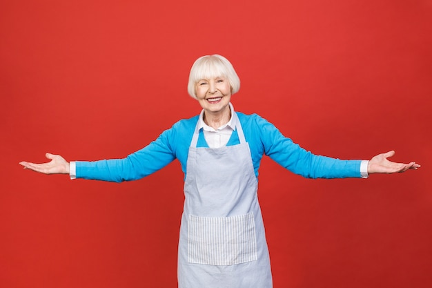 赤の背景に分離されて立っているエプロンの年配の女性。彼女はいい主婦です。彼女はおいしい料理を作るのが好きです。