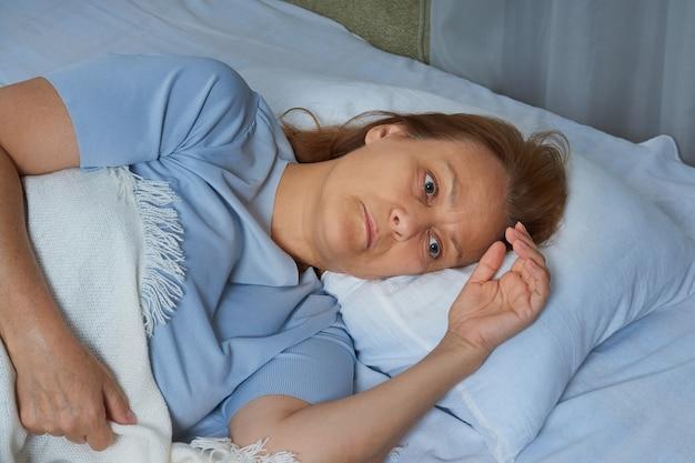 Старшая женщина в синей пижаме, лежащая в постели, страдающая бессонницей