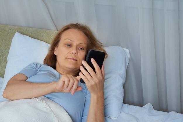 침대에 누워있는 동안 휴대 전화를 사용하는 파란색 잠옷 수석 여성