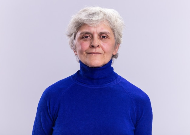 白の上に立っている真剣な自信を持ってカメラを見ている青いタートルネックの年配の女性
