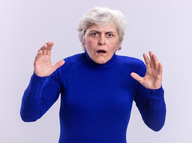 心配し、白い背景の上に立って腕を上げて混乱しているカメラを見て青いタートルネックの年配の女性