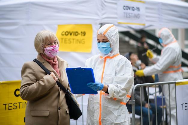 Covid-19 테스트 센터의 수석 여성은 야외에서 도시 거리, 코로나바이러스 개념입니다.