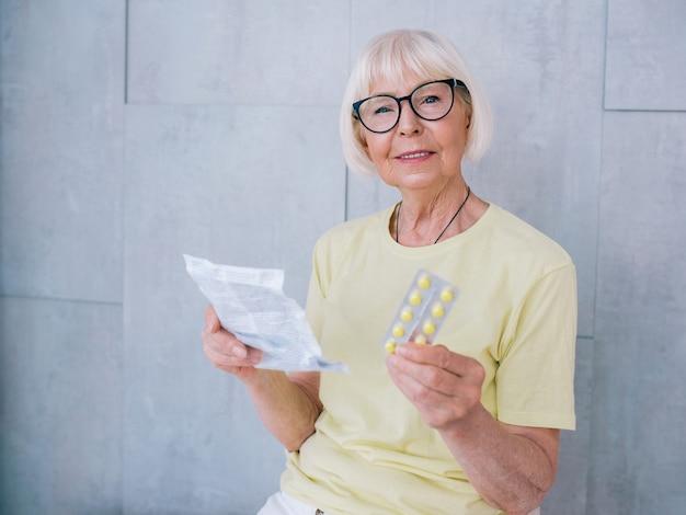 Старшая женщина в очках читает инструкцию по лекарствам и таблеткам возраст здравоохранения