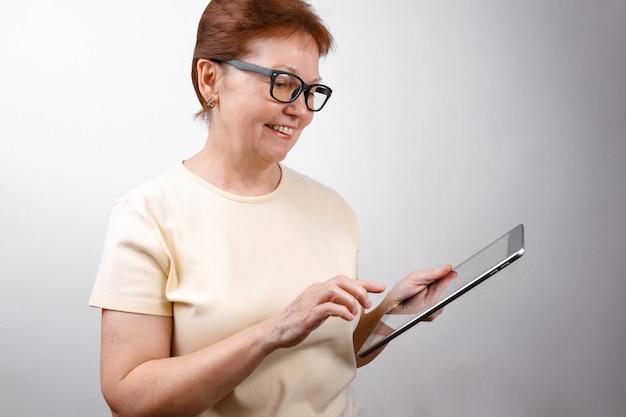 メガネの年配の女性が白いtシャツに白のタブレットを使用してください。