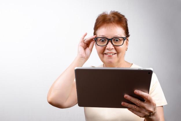 軽いtシャツに白のタブレットでメガネで年配の女性