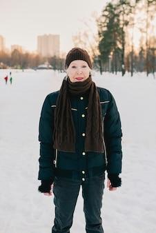 雪の冬の公園でジョギング帽子とスポーティなジャケットの年配の女性