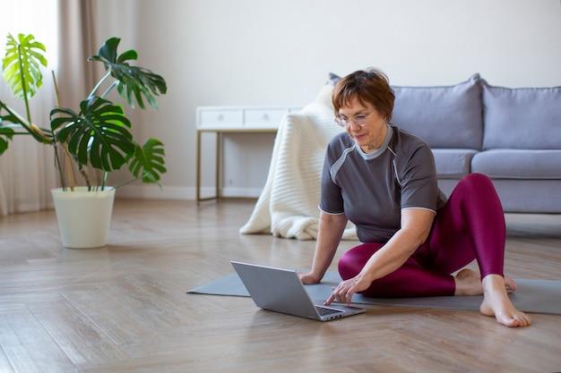 ヘッドフォンの年配の女性は、インターネットでのトレーニングの準備をしています。彼女はインターネットでエクササイズビデオを検索しています。