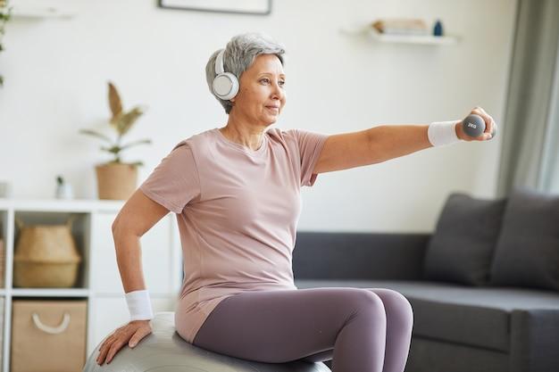 Старшая женщина в наушниках сидит на фитнес-мяче и тренируется в гостиной дома