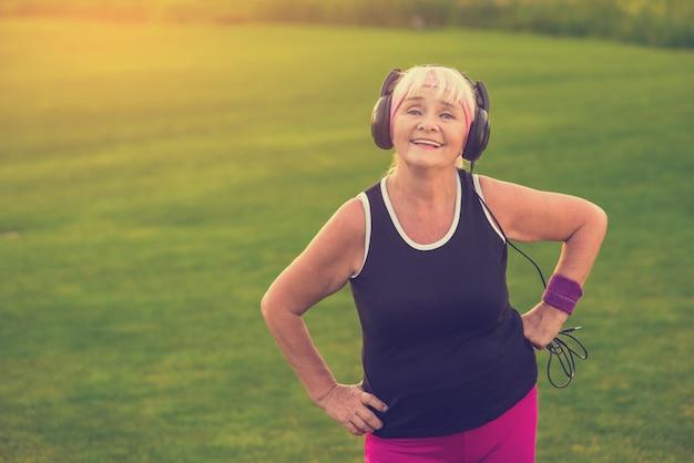 Старшая женщина в наушниках Premium Фотографии