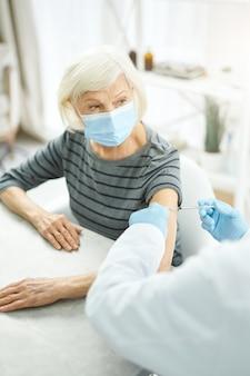 コロナウイルスワクチンの投与を受けている医療マスクの年配の女性