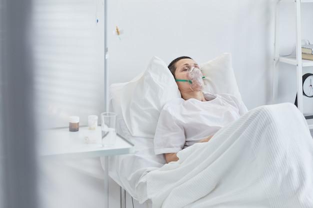 Старшая женщина в кислородной маске, лежа на кровати в реанимации