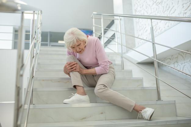 膝を傷つけて階段に座っているピンクのシャツの年配の女性