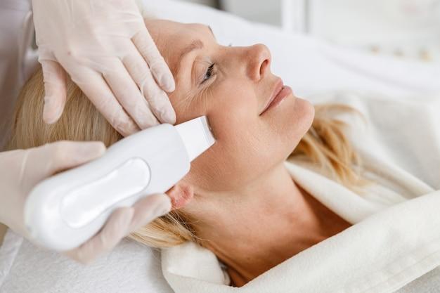 Старшая женщина в профессиональном спа-салоне красоты во время процедуры ультразвуковой чистки лица.