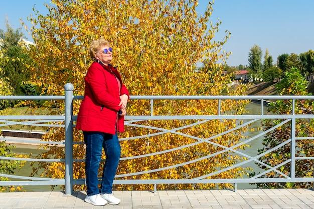 公園で自然の中で歩いてリラックスして赤いジャケットを着た年配の女性。秋の天気