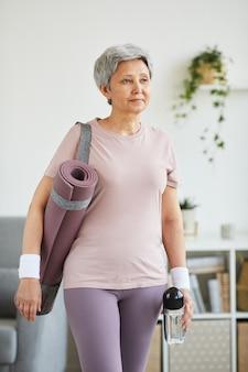 Старшая женщина в спортивной одежде и с ковриком для упражнений, стоящим в домашней комнате