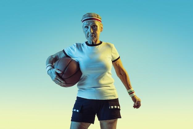 グラデーションの背景、ネオンライトでバスケットボールをするスポーツウェアの年配の女性。素晴らしい形の女性モデルはアクティブなままです。スポーツ、活動、動き、幸福、自信の概念。コピースペース。
