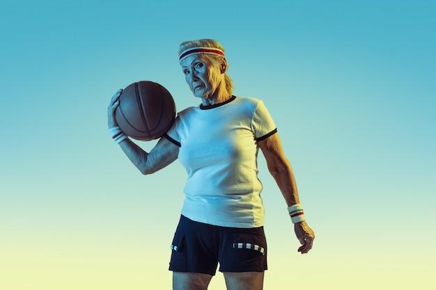 勾配の壁でバスケットボールをするスポーツウェアの年配の女性