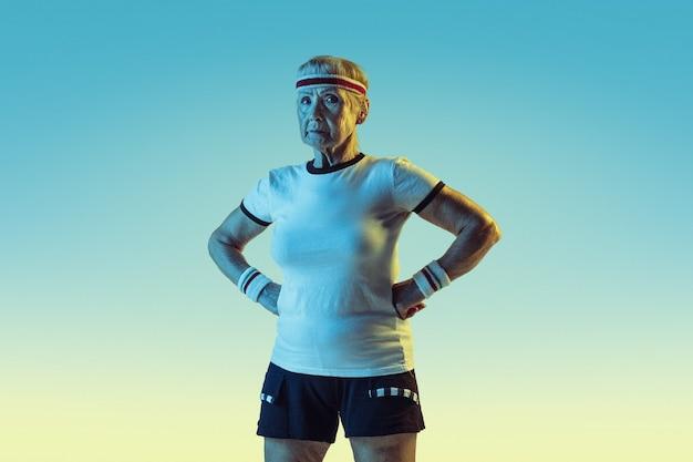 Старшая женщина в спортивной тренировке и позирует на градиентной стене