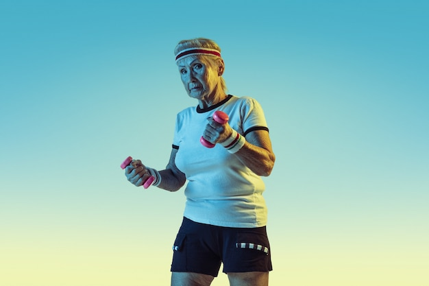 Старшая женщина в спортивной тренировке с весами на градиентной стене