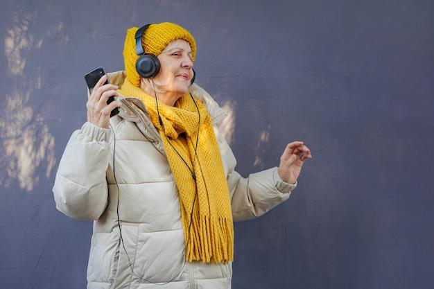 헤드폰으로 음악을 듣고 춤을 추는 세련된 겉옷을 입은 고위 여성